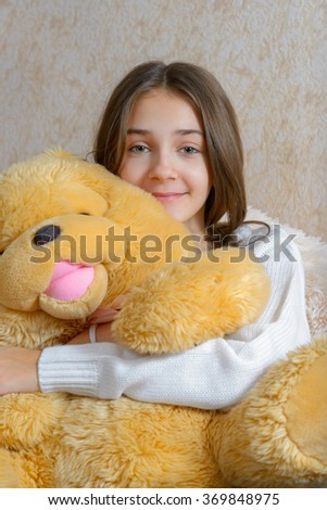 Girl with toy sitting on the couch with a fur coverlet