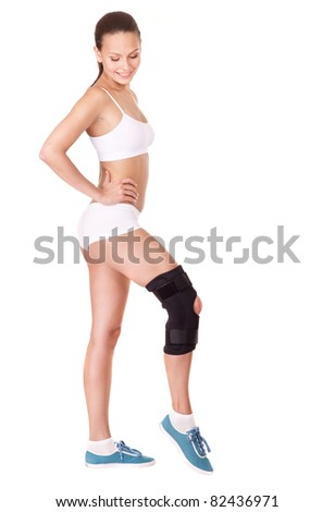 Girl with trauma of knee in brace.. Isolated. - stock photo