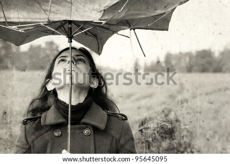 girl with umbrella. girl in the field. Photo in old color image style. - stock photo