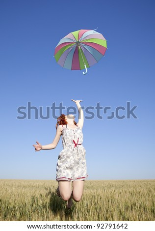 Girl with umbrella jumping at field