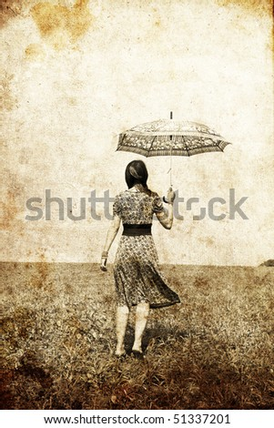 Girl with umbrella on field. Photo in old image style.