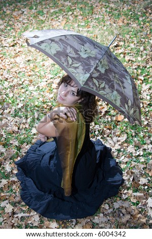 Girl with umbrella sitting at autumn park and posing. - stock photo