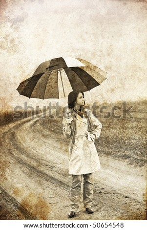 Girl with umbrella staying on village road near field. Photo in old image style.