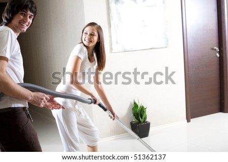 Girl with vacuum cleaner and boy - stock photo