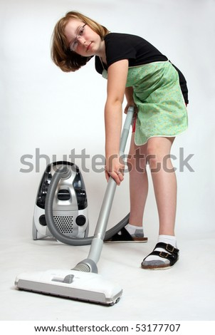 Girl with vacuum cleaner on light grey background - studio shot. - stock photo
