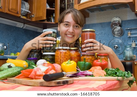Girl with vegetables and jars in the kitchen