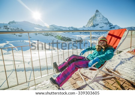 Girl with view of Matterhorn on a clear sunny day - Zermatt, Switzerland, winter vacation - stock photo