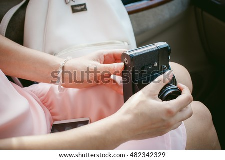 girl with vintage camera in his hands. sitting in the car, the girl in a pink dress holding a retro camera, ready to shoot him
