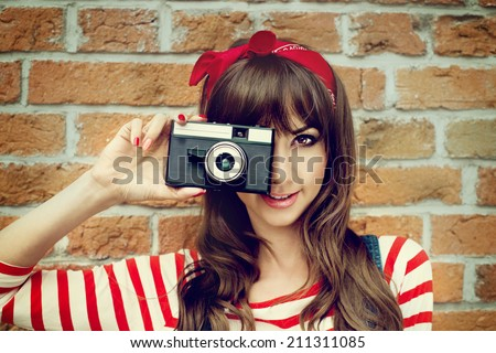 Girl with vintage camera taking photo on brick wall background. Selfie - stock photo