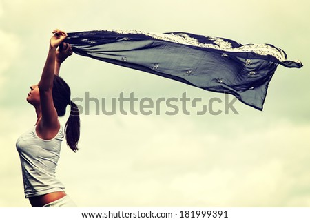 Girl with voile against cloudy sky