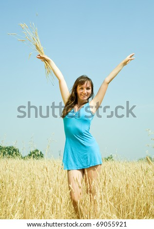 Girl with  wheat ears at wheat field in summer