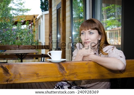 girl with white cup on the veranda of the house. girl drinking tea, a woman with a cup of coffee  - stock photo