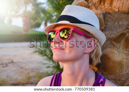 Girl with white hat leaning on a palm tree trunk with nice sunset reflection in the pink sunglasses