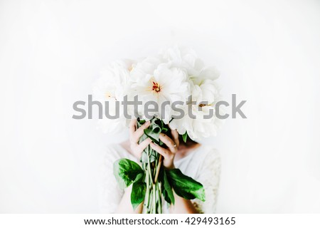Girl with white peonies bouquet at white wall - stock photo