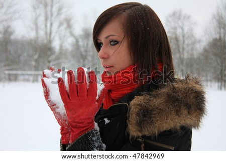 Girl with white snow in her hands - stock photo