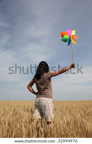 Girl with wind turbine at wheat field - stock photo