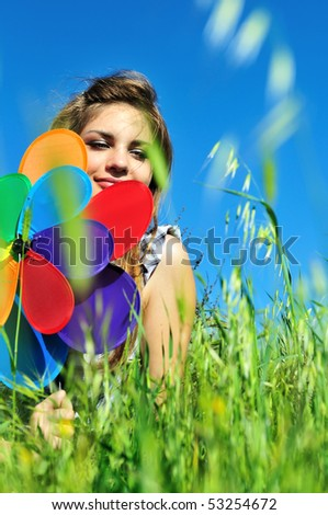 girl with windmill sitting in the grass