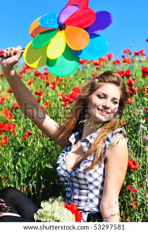 girl with windmill sitting in the poppy field - stock photo