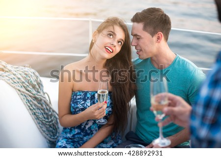 Girl with wineglass and guy. Young couple sitting on yacht. Sweet moments of romance. Head in the clouds. - stock photo