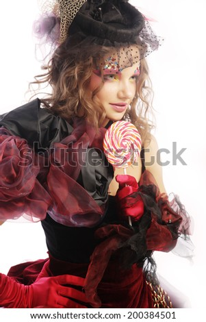 Girl with with creative make-up holds lollipop. Doll style. - stock photo