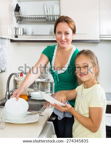 Girl  with woman washing plates in kitchen - stock photo