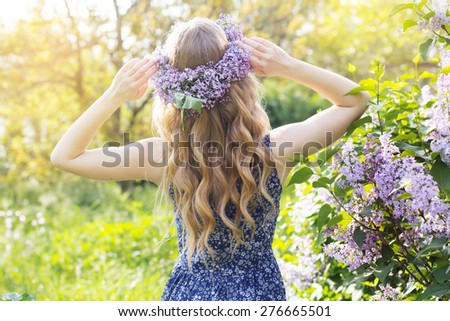 Girl with wreath from lilac purple flowers in green park, spring time - stock photo
