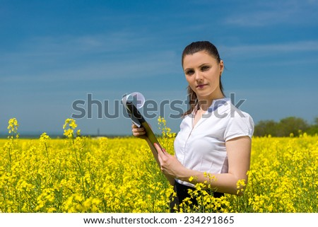 girl with yellow flowers and file on the field - stock photo