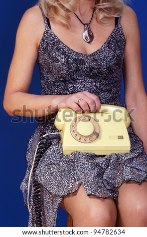 girl with yellow telephone set on blue background