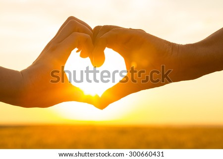 Girl woman's hands in shape of heart. Heart shaped hand silhouette made against the orange yellow sun, sky of a sunrise or sunset. Love and care, freedom concept. Outdoors life style close up portrait - stock photo