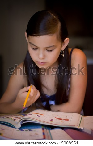 Girl working on a homework with books in front of her - stock photo