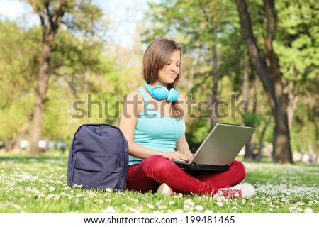 Girl working on a laptop in the park seated on green grass - stock photo