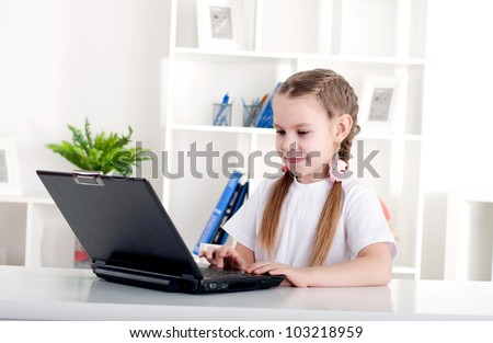 girl working on laptop at home, sitting at the table - stock photo