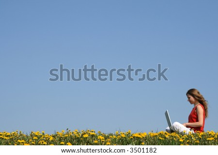 Girl working with laptop outdoors in a flowering spring field. - stock photo
