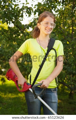 Girl works with cordless grass trimmer in garden - stock photo