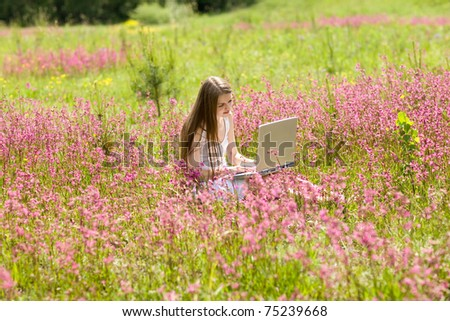 Girl works with wi-fi solution in beautifl meadow full of flowers - stock photo