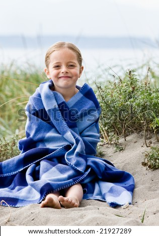 Girl wrapped in blanket at beach - stock photo