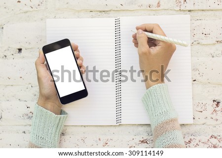 Girl writes in a diary with blank cell phone, mock up - stock photo