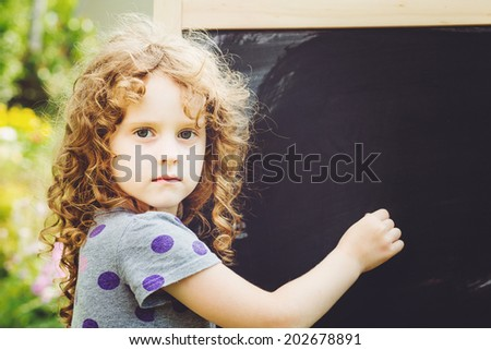 Girl writes in chalk on a blackboard. Education concept. Toning photo. - stock photo