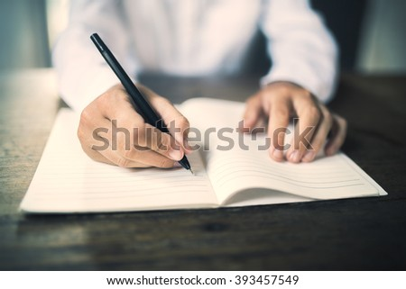 Girl writes in notebook on a wooden table