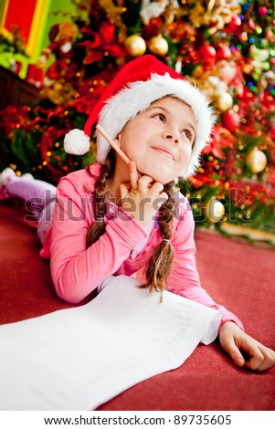 Girl writing a letter to Santa with her Christmas wishes