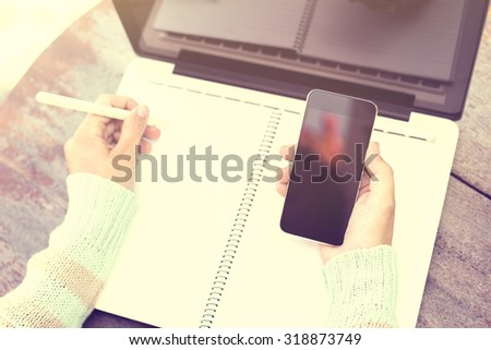 girl writing in a notebook with a cell phone and a laptop - stock photo