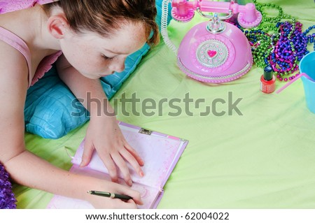 Girl writing in journal - stock photo