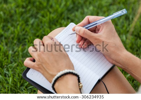 Girl writing in notebook on the green grass background - stock photo