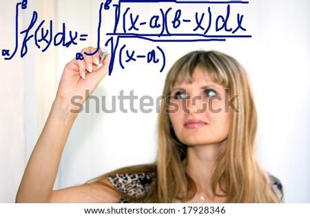 girl writing math formulas on a white-board - stock photo