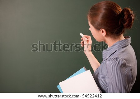 girl writing on a chalkboard - stock photo