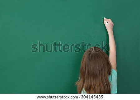 Girl Writing With Chalk On Green Chalkboard In Classroom