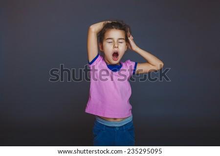 girl yawns wants to sleep on a gray background - stock photo