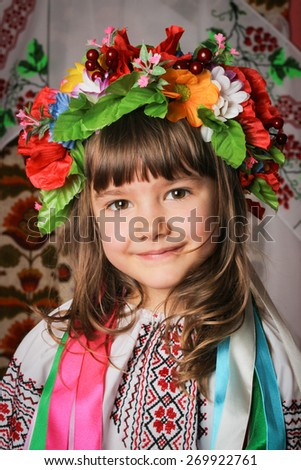 Girl 6-7 years brunette in Ukrainian national costume in a wreath with ribbons - stock photo