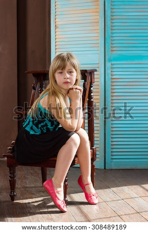 Girl 6 years old in a dress sits on a chair near the blue wall - stock photo