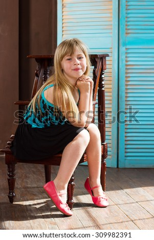 Girl 6 years old in dress sits on a chair near the blue wall - stock photo